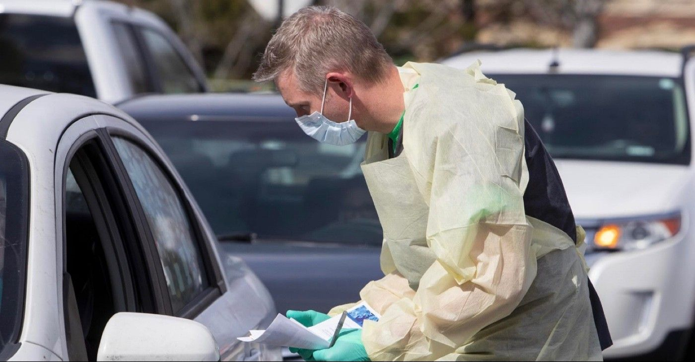 Cullen Anderson, RN, screens people in a line of cars waiting to be tested for coronavirus COVID-19 at a drive-thru testing station in Idaho