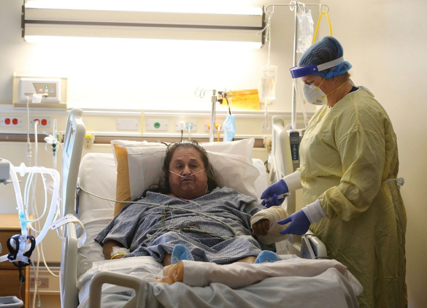 Memorial Hospital nurse Angela Bilyeu flushes the IV of patient Pedro Cortez in a COVID-19 unit on Friday | Alex Horvath