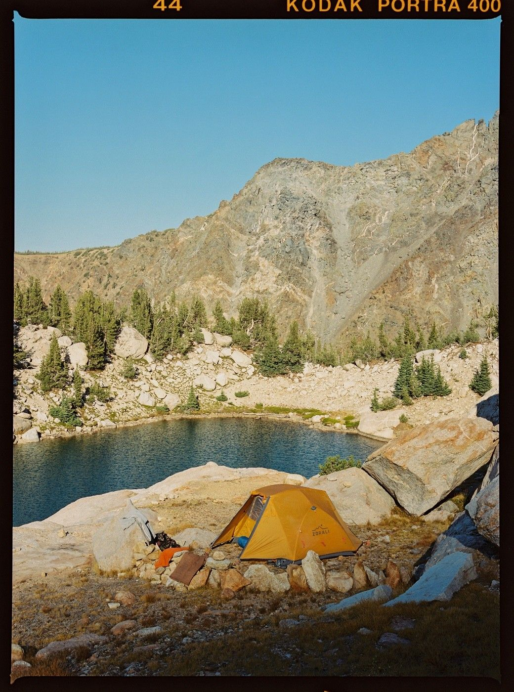 FRAME 12 — Camp for the night, nestled into a cliff edge overlooking an alpine lake. Not too shabby.